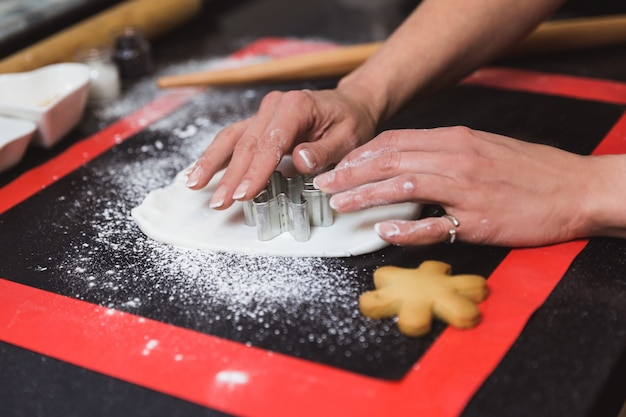 Woman decorates christmas gingerbread cookies with icing sugar glaze snowflake. christmas gift, homemade gingerbread