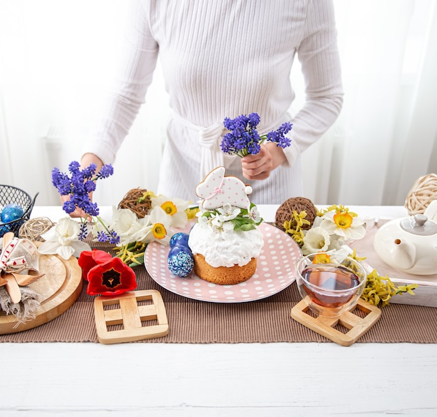 A woman decorates a table with plowing treats with flowers. easter holiday concept.