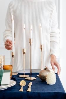 キャンドルでエレガントなダイニングテーブルを飾る女性