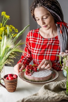 딸기 케이크를 장식하는 여자