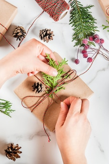 Woman decorating christmas gift or present box, with christmas tree branches, pine cones, red berries, on white marble table, or to do list in notebook, with coffee mug, copy space top view