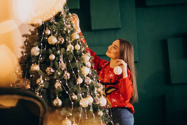 Woman decorating christmas tree on christmas