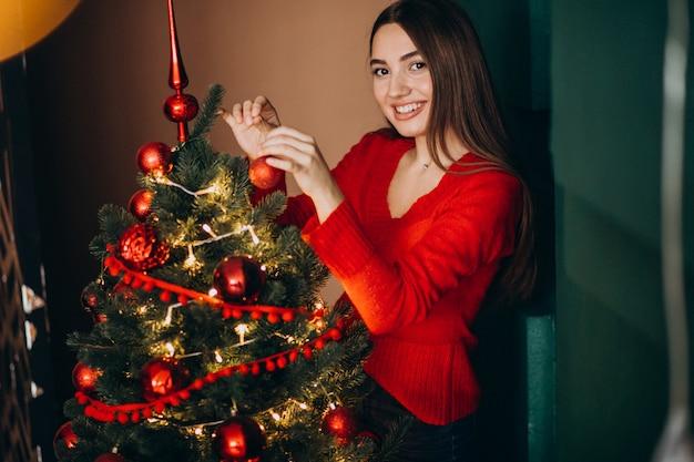 Woman decorating christmas tree on christmas