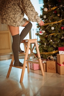 Woman decorating Christmas tree with bauble