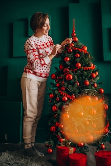 Woman decorating christmas tree with red balls