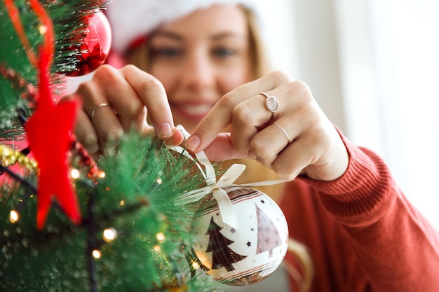 Woman decorating the christmas tree with a white ball