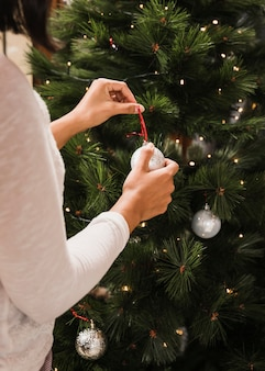 Woman decorating the christmas tree with white balls
