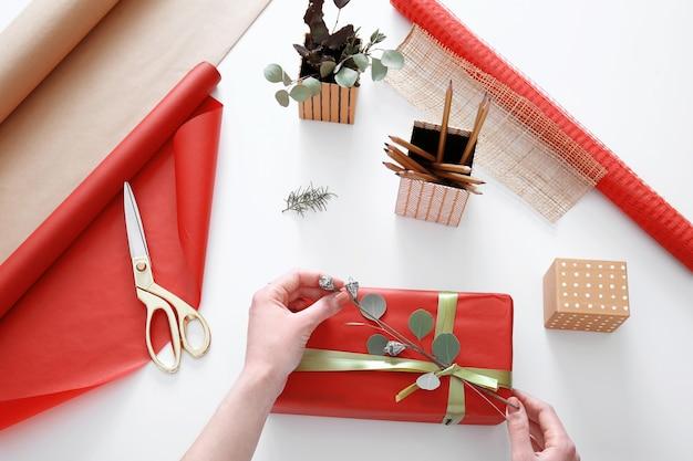 Женщина украшает подарочную коробку на столе