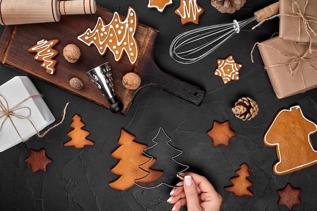ジンジャーブレッドのクリスマスクッキーを粉砂糖で飾る女性のクリスマスの準備のコンセプトトップv ...