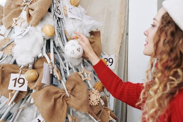 彼女のクリスマスツリーを飾る女性
