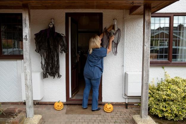 ハロウィーンのために彼女の家を飾る女性