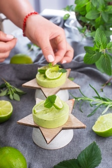 Woman decorating organic matcha green desserts with natural raw ingredients