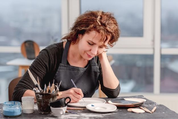手作りのパターンでプレートを飾る女性