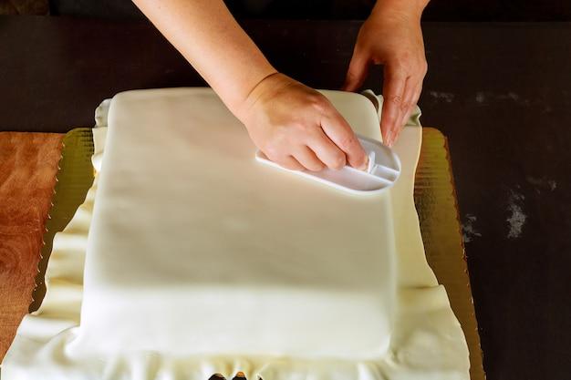 白いフォンダンで正方形のケーキを飾る女性。ウエディングケーキの作り方。
