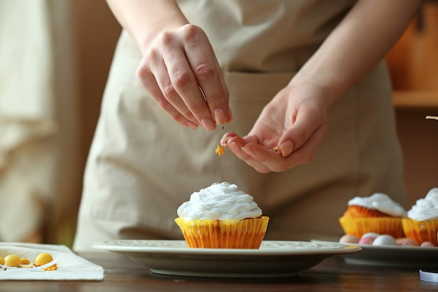 Woman decorating tasty easter cupcake