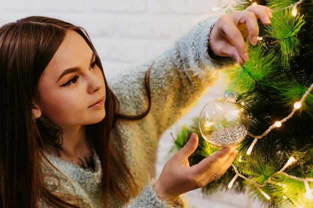 Женщина украшает елку