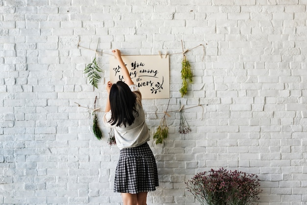A woman decorating the wall with flowers