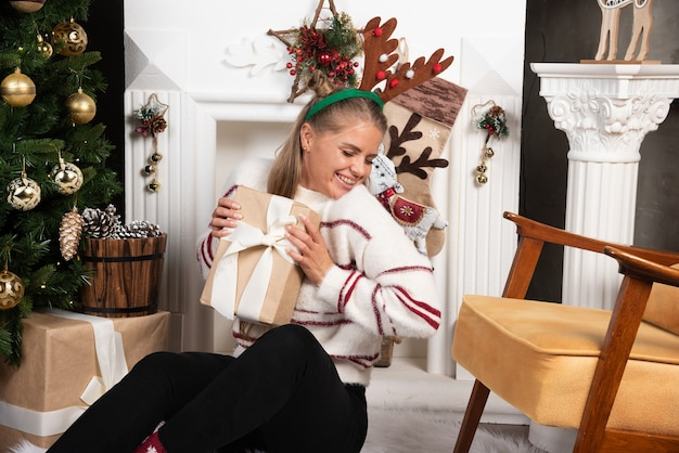 Woman in deer ears showing present in christmas interior design.