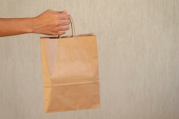 Woman delivering cardboard shopping bag with space for text.