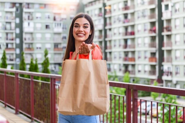 紙袋に食べ物を提供する女性。宅配フードサービス。宅配便は、名前のないバッグ付きの食品を注文しました。