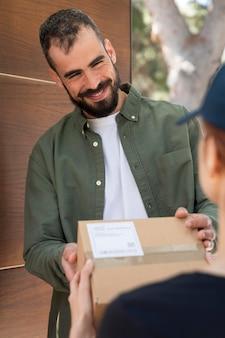 Donna che consegna un pacchetto per un uomo