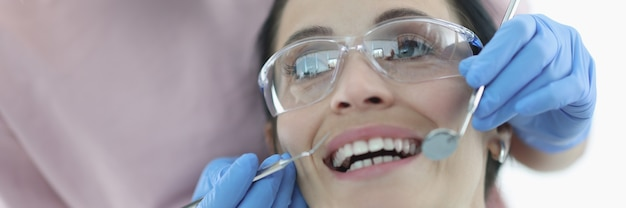 여자는 치과 약속에서 그녀의 이빨을 보여줍니다