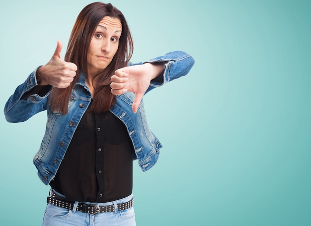 Woman in denim jacket with one thumb up and one down