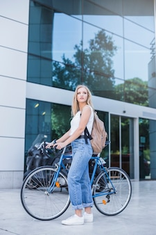 Woman in denim jeans and top standing with bicycle near the building