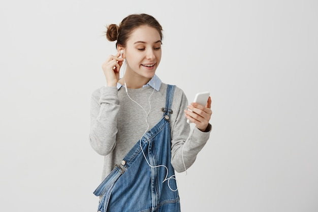 Woman in denim overalls being relaxed using smartphone watching videos from internet. adult girl listening music via headphones with smile. technology concept