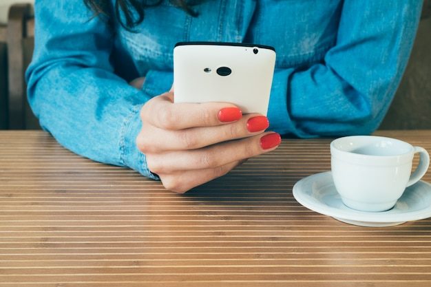 Woman in a denim shirt uses a smart phone in cafe