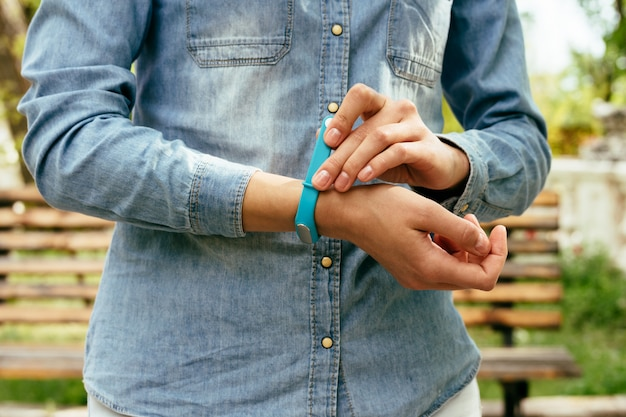 Woman in denim shirt wears sports wristband for measuring steps