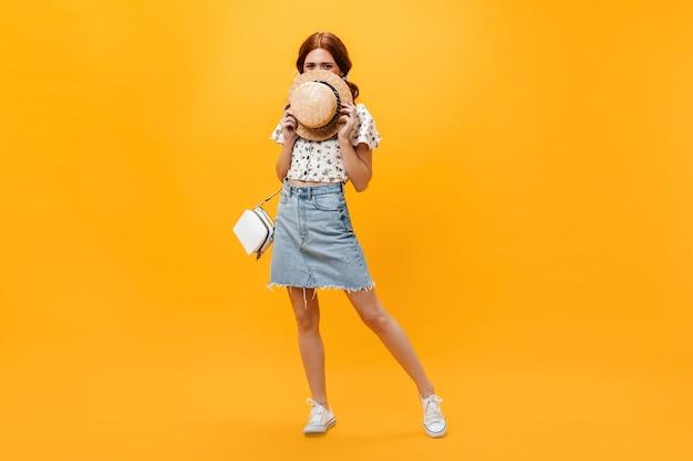 Donna in gonna di jeans e top corto bianco copre il viso con il cappello e guarda nella telecamera su sfondo arancione.