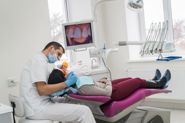 Woman in dentist chair and doctor with tool