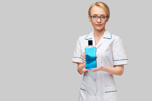 Woman dentist doctor holding bottle of mouthwash