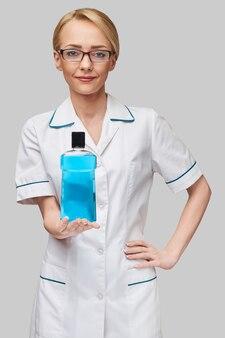 うがい薬のボトルを保持している女性歯科医