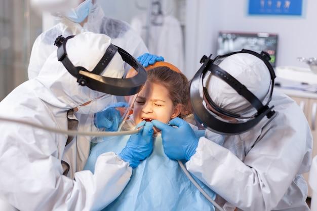痛みの表情で小さな女の子の歯を治療する女性歯科医。子供の歯の処置をしているcovid19の間にppeスーツを着ている口腔病学チーム。