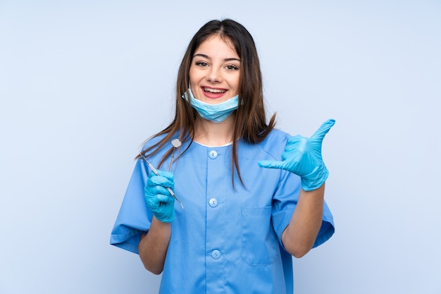 Woman dentist holding tools over blue wall making phone gesture
