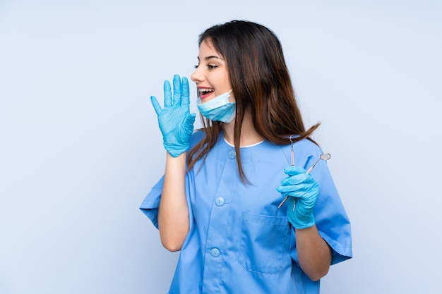 Woman dentist holding tools over blue wall shouting with mouth wide open