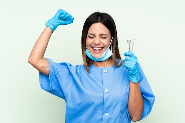 Woman dentist holding tools over green wall celebrating a victory