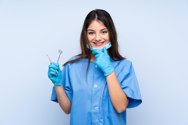 Woman dentist holding tools over isolated blue wall laughing