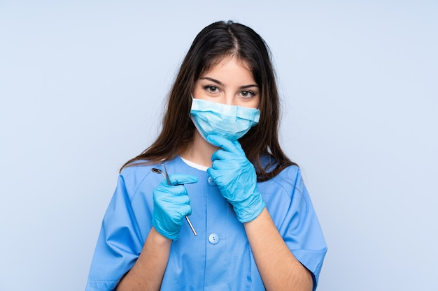 Woman dentist holding tools over isolated blue wall