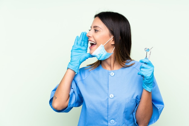 Woman dentist holding tools over isolated green wall shouting with mouth wide open