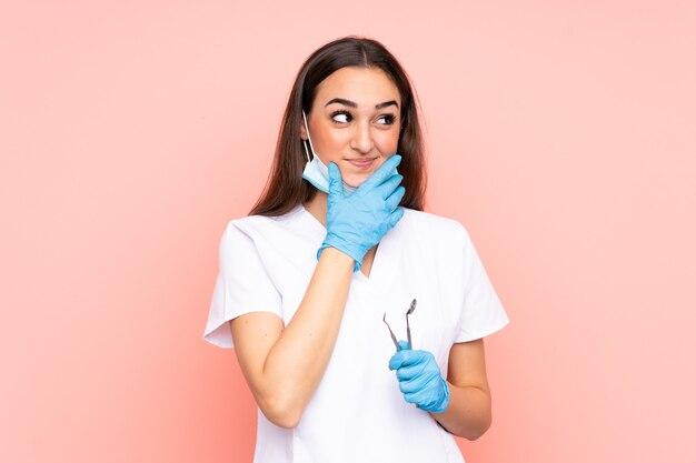 アイデアを考えてピンクの背景に分離されたツールを保持している女性の歯科医