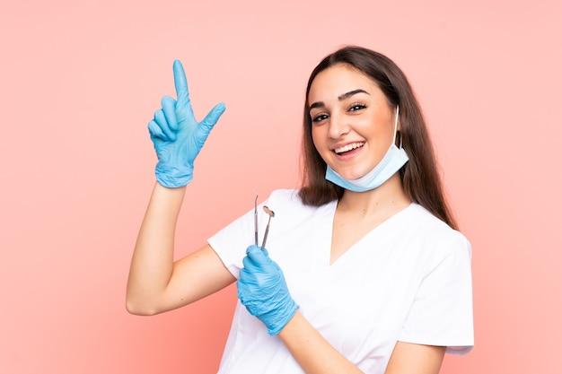 검지 손가락으로 가리키는 분홍색 벽에 고립 된 도구를 들고 여자 치과 의사 좋은 아이디어