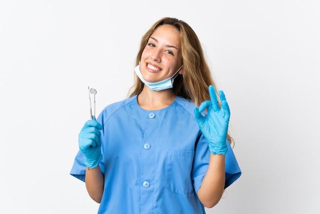Женщина-стоматолог, держащая инструменты, изолированные на белом, показывает знак ок пальцами