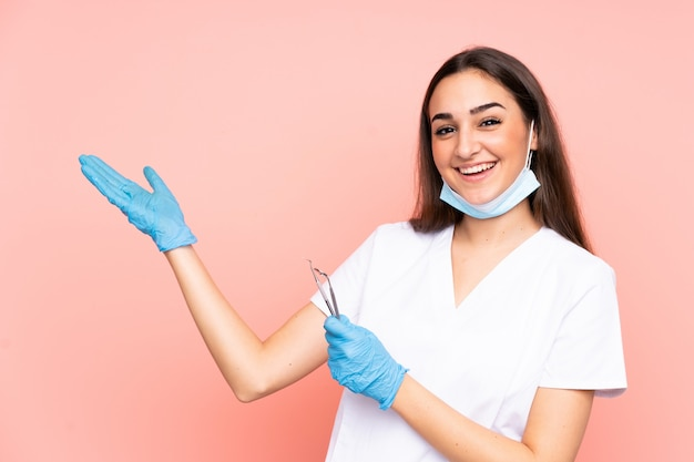 Woman dentist holding tools isolated on pink extending hands to the side for inviting to come