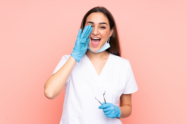 Woman dentist holding tools isolated on pink shouting with mouth wide open