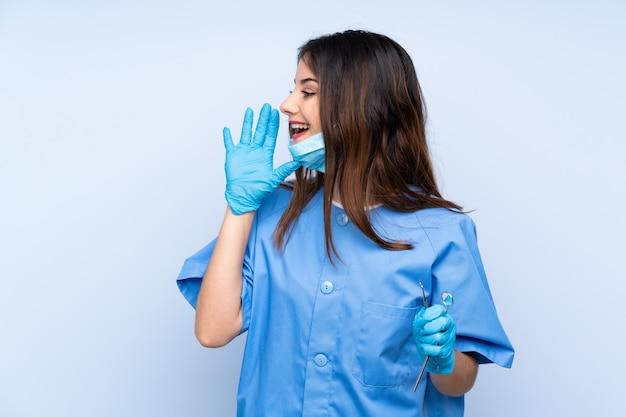 Woman dentist holding tools over isolated wall