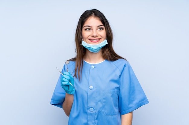 Woman dentist holding tools laughing and looking up