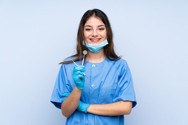 Woman dentist holding tools laughing